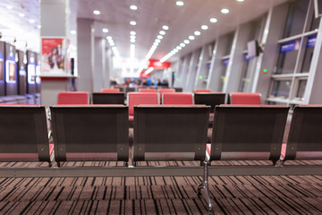 Empty armchairs in hall of expectation of airport and plane behind window