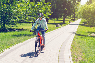 A cyclist in a helmet rides a bicycle path