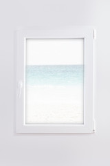closed white window with blue sea and white beach in background