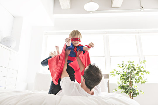 Father and son play superheroes on bed at home.