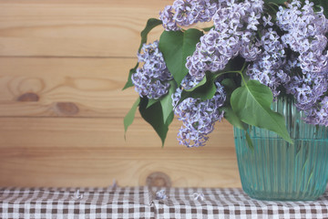 Bouquet of purple lilac in a vase. space for text.