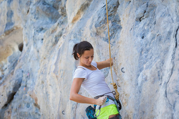 Young woman rock climbing on white mountain