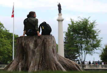 Woman sits on tree stump before a march during the G7 Summit in Quebec City