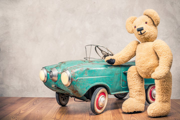 Teddy Bear standing near rusty outdated retro turquoise toy pedal car in front concrete textured wall background. Vintage style filtered photo