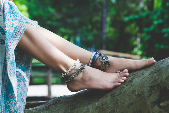 woman summer boho fashion style details on barefoot anklets and rings outdoor