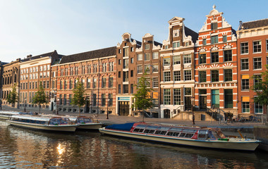 Typical old houses of Amsterdam under blue sky.