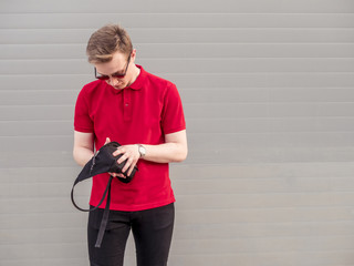 isolated young hipster holding his bag outdoors