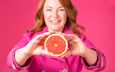 Beautiful adult woman, blurred face, holding forward juicy grapefruit. Joyful woman on the pink background. People on a diet. Citrus is the best remedy for autumn colds.