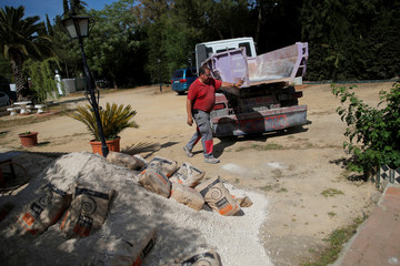 "A truck driver of ""BigMat La Toma"" closes a trailer after unloading sand and cement bags from it at the home of a customer in Ronda"