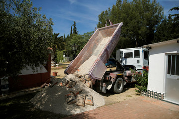 "A truck driver of ""BigMat La Toma"" unloads sand and cement bags from a trailer at the home of a customer in Ronda"