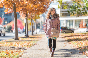 Young happy woman walking on sidewalk street in Washington DC, USA United States legs in alley of golden orange yellow foliage autumn fall trees on road during sunny day Wall mural
