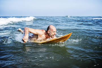 A senior man on a surfboard