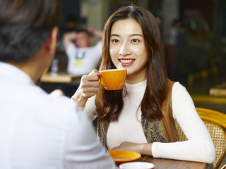 young asian couple talking face to face in coffee shop