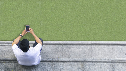 the top aerial view of the man in white shirt uses mobile phone and sits on the pedestrian concrete walk way at glass green landscape.