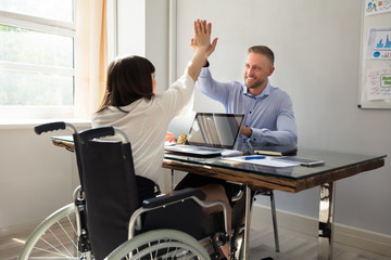 Disabled Businesswoman Giving High Five To Her Partner