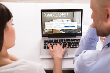 Couple Searching Online Hotels On Laptop