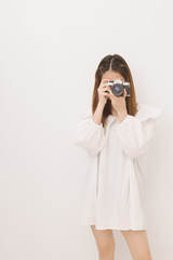 Portrait of young asian woman holding vintage camera for take a photo, Woman photographer in action on white background.