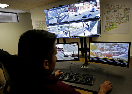An officer observes computer screens displaying images from cameras monitoring traffic condition, general monuments and public areas, at the Office of Public Security and Traffic in Monterrey