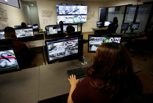 Officers observe computer screens displaying images from cameras monitoring traffic condition, general monuments and public areas, at the Office of Public Security and Traffic in Monterrey
