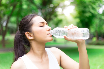 Woman drinking water during a running. Jogging woman in Park. Sunny day. Drinking mode.