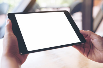 Mockup image of hands holding and using a black tablet pc with blank white desktop screen