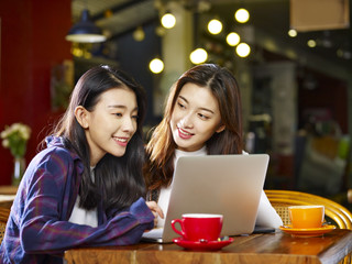 two young asian women using laptop in coffee shop
