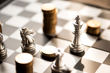 chess pieces and stack of coins on a chessboard, business strategy concept