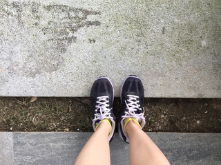 Female in Purple Sneakers Shoes Isolated. Top View. Woman Wear Runner Sneakers Urban on Cement Background
