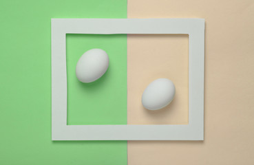 Chicken eggs in a white frame on a colored pastel background. Minimalist trend..