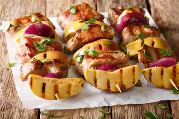 Rustic juicy kebabs of pork with apples and red onions close-up on parchment. horizontal