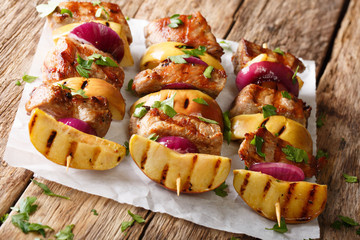 Tasty skewers of pork with fresh apples and red onions close-up on paper. horizontal