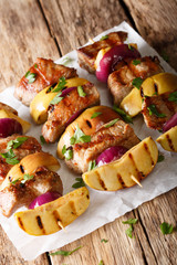 Homemade pork kebabs with apples and red onions on skewers close-up. vertical