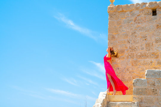 Beautiful girl in a long pink dress standing on the edge of the white cliffs by the Church of St Mary Magdalen on the island of Malta