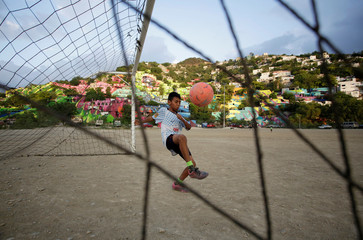A young man kicks a ball in front of colorful painted houses on the side of a hill in neighbourhood Cerro de la Campana