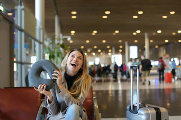 Smiling female person sitting with neck pillow and luggage in airport waiting room. Concept of traveling abroad and gladden passenger.
