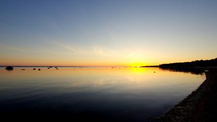Piękny zachód słońca nad bałtyckim morzem, przy niebiańskiej plaży