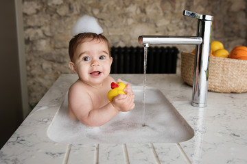 Baby taking bubble bath in kitchen sink holding rubber duck