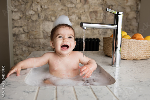Laughing Baby Taking Bubble Bath In Kitchen Sink Stock