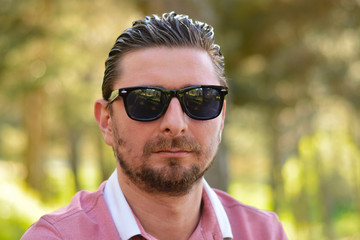 Young man's outdoors portrait looking at the camera who has sunglasses with natural green background. Neutral, happy, sad, disgust, fear, surprise Facial Emotion.