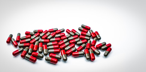 Pile of red and grey capsule pills isolated on white background with copy space. Flunarizine : drug for migraine prophylaxis treatment. Global healthcare concept. Pharmaceutical industry concept.