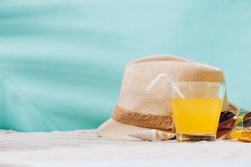 Summer background. Beach accessories flip flops, sunglasses, hat and orange juice on sand background