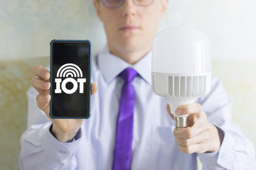 Internet of things (IoT) Mobile Information Technology. Man offers a smartphone with IOT icon and light bulb.