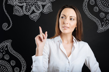 Good idea. Professional experienced teacher looking elegant and putting her finger up while thinking about an unusual idea