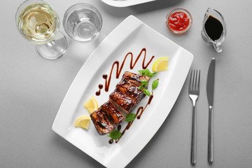 Plate with delicious grilled ribs and sauce on table