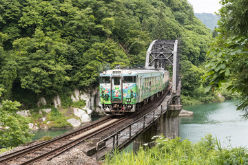 FUKUSHIMA, JAPAN - June 18 : The local train Tadami line and Tadami river on June 18 , 2017 in Fukushima , Japan. This train services in East Japan railway company's Tadami line.