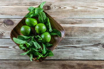 Fresh mint leaves and green limes in a wooden dish on a wooden background. Top view