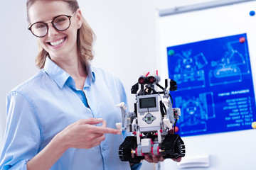 Modern engineering. Joyful smart female engineer holding a robot and smiling while being happy about successful invention