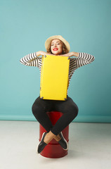 Young happy beautiful woman in hat holding yellow suitcase over blue background