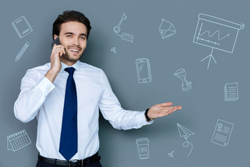 Friendly web developer. Positive enthusiastic web developer feeling happy and smiling while talking on the phone with a colleague