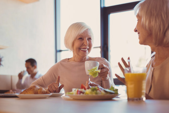 Best friends. Two pleasant cheerful elderly women sitting in cafe and talking, discussing the news, while drinking coffee and eating salad